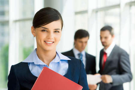 Portrait of confident female looking at camera with her colleagues at background Stock Photo - 8455186