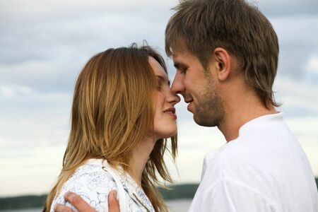 passionate kiss: Portrait of loving couple on a sky background