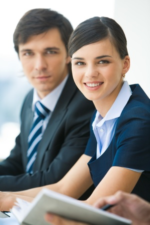 serious business: Portrait of attractive business lady looking at camera with smile on background of serious man