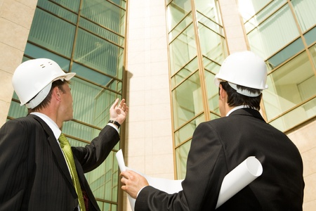 Portrait of customer showing building to architect photo