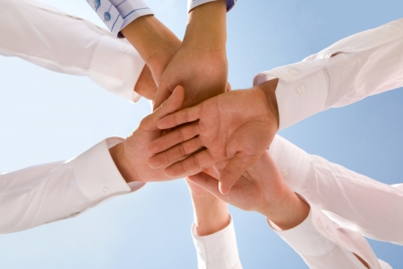 workgroup: Bottom view of people hands holding together on a sky background