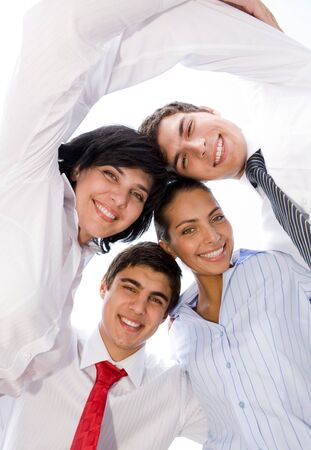 Portrait of smiling group in white shirts together looking at camera  photo