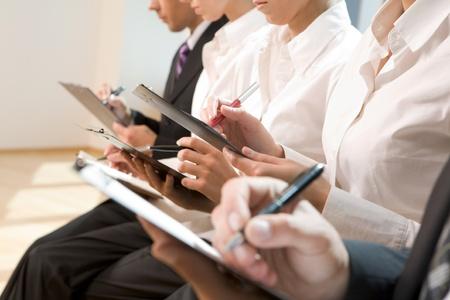 reportero: Imagen de fila de gente de negocios, escribiendo sobre documentos en seminario Foto de archivo