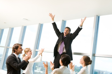 Photo of successful businessman raising his arms and shouting surrounded by his colleagues applauding photo