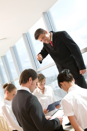 Angry ceo shouting at his employees surrounding him at meeting Stock Photo - 8475011