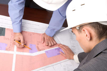 executive helmet: Above view of engineers over blueprints during discussion Stock Photo