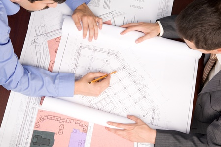 preliminary: Above view of engineers over blueprints during work planning