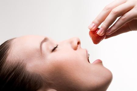 boca abierta: Imagen de chica bonita con abrir la boca y fresa madura en la mano