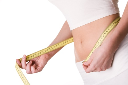 measure waist: Close-up of female belly with measuring tape around it
