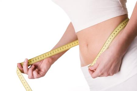 metro de medir: Primer plano de vientre femenino con cinta alrededor de medici�n