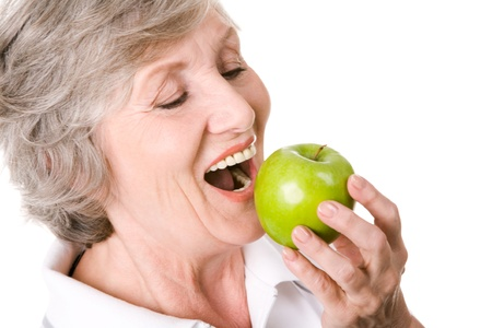 senior eating: Portrait of senior woman holding an apple and eating it