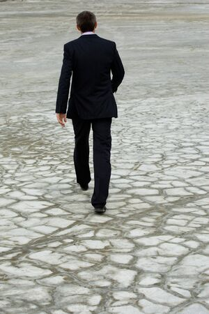 Rear view of man in suit walking down dry ground photo