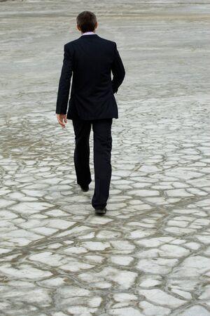caminando: Vista posterior del hombre con traje caminando por tierra seca Foto de archivo
