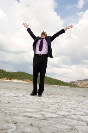 Photo of elegant businessman standing and raising his arms outdoors in summer photo