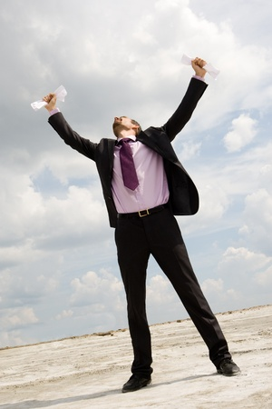 Photo of crying businessman standing and raising his arms with papers outdoors photo