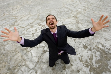 Photo of crying businessman standing on dry ground and raising his arms upwards photo