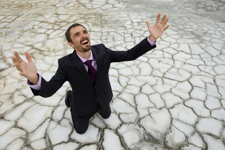 СОС: Photo of helpless businessman standing on dry ground and raising his arms upwards
