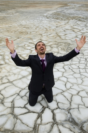 Photo of helpless businessman standing on dry ground and screaming with raised arms photo