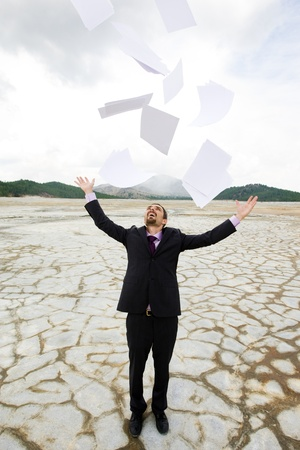 Photo of delighted businessman standing and throwing papers outdoors photo