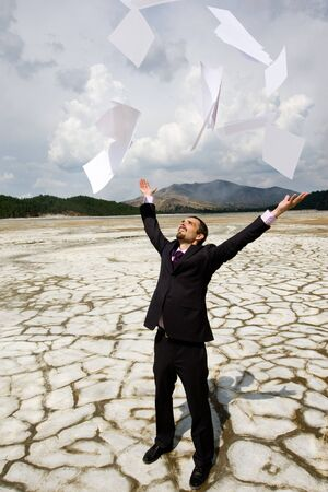 hands   free: Photo of happy businessman standing on dry ground and throwing papers upwards