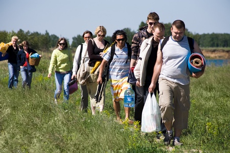 Image of queue of tourists walking down green grass while on trip outdoors photo