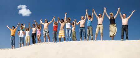 line up: Image of many friends standing on sandy beach with their arms raised against blue sky Stock Photo