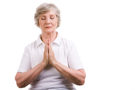 eyes shut: Portrait of mature woman praying with her hands put together and eyes shut Stock Photo