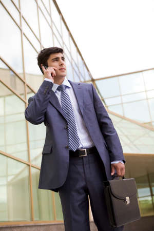 Portrait of confident businessman communicating by cellular phone outdoors photo