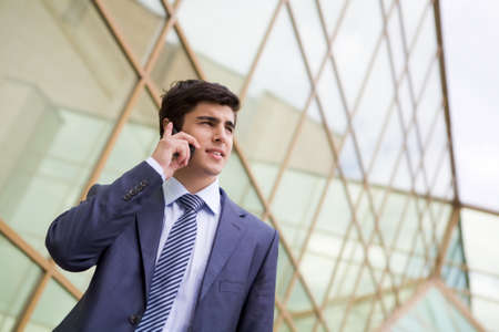 Portrait of confident businessman communicating by cellular phone outdoors Stock Photo - 8479171