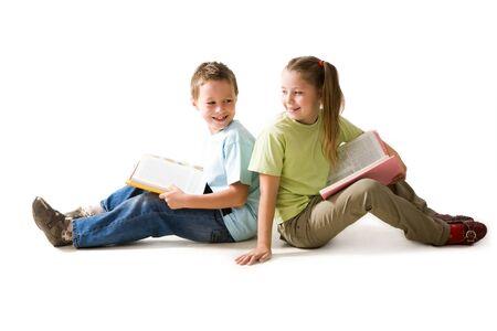 ni�os pensando: Retrato de los escolares lindos sentada en el suelo con libros abiertos
