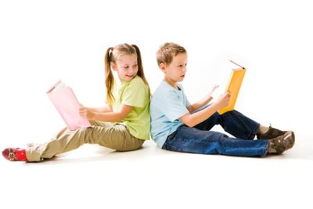smart boy: Portrait of cute schoolchildren holding open books and reading them