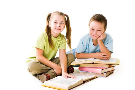 pile of books: Portrait of cute schoolchildren looking at camera during reading books