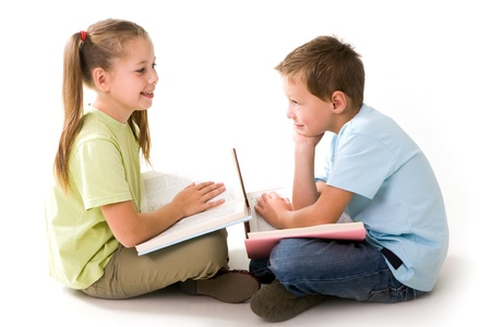 children talking: Portrait of cute schoolchildren holding open books and communicating Stock Photo