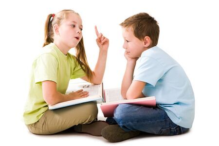 lad: Portrait of cute schoolgirl explaining something to pensive lad who listening to her attentively