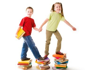 diligente: Ni�os en edad preescolar diligentes de pie en lo alto de las escaleras de libro Foto de archivo