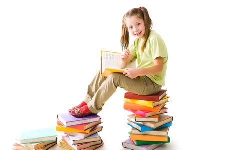 readers: Portrait of cute schoolgirl sitting on top of heap with open book and looking at camera