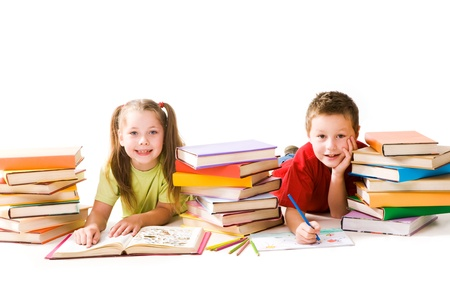 clever: Portrait of cute schoolchildren looking at camera while reading book and drawing