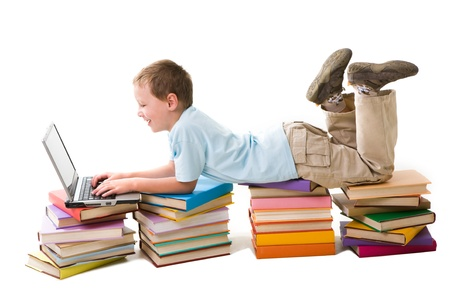 Portrait of cute schoolboy lying on top of book stacks and typing on laptop keyboard photo