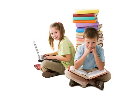 the pupil: Smart girl with laptop and cute schoolboy with book sitting back to back and looking at camera
