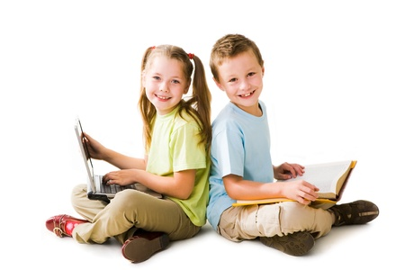 educational: Smart girl with laptop and cute schoolboy with book sitting back to back and looking at camera