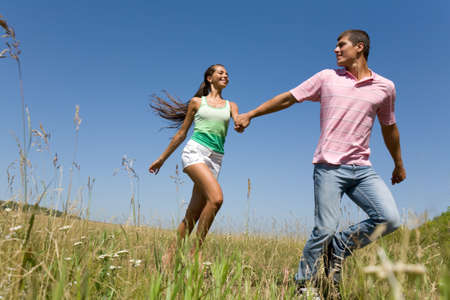 oung man and woman holding each other by hands and running outdoors photo