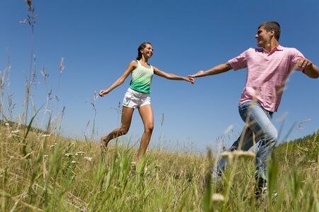 free running: Photo of young couple running down green grass in the countryside