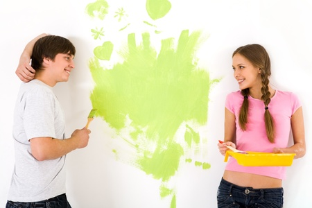 Affectionate couple looking at each other while painting walls in new house photo
