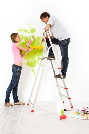 Affectionate couple helping each other to paint walls in new house Stock Photo - 8477733