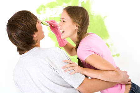 Image of joyful girl painting lad�s face with green color while both laughing during improvement of flat Stock Photo - 8479189