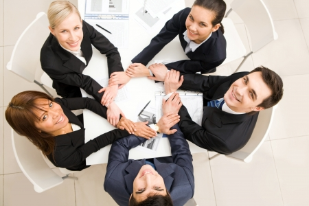collaboration: Above view of business team with their hands making circle looking upwards Stock Photo