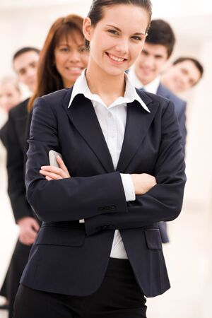 spokesperson: Portrait of successful businesswoman looking at camera on background of several employees Stock Photo