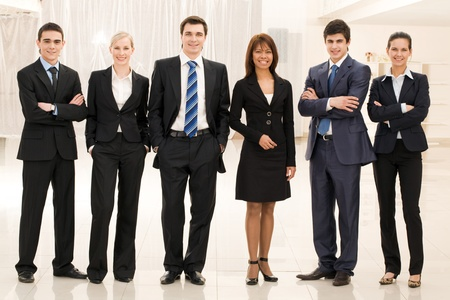 workgroup: Portrait of confident business group standing in row and looking at camera