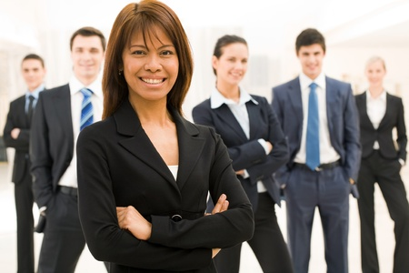 workteam: Portrait of successful businesswoman looking at camera with her workteam at background