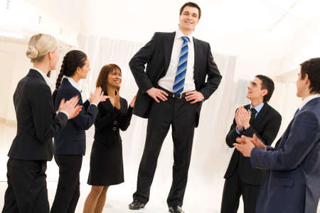 woman boss: Photo of happy business partners applauding to confident leader surrounded by them Stock Photo